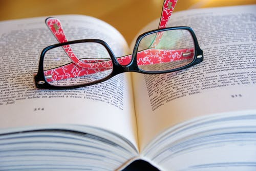 Black Framed Eyeglasses on Book Page