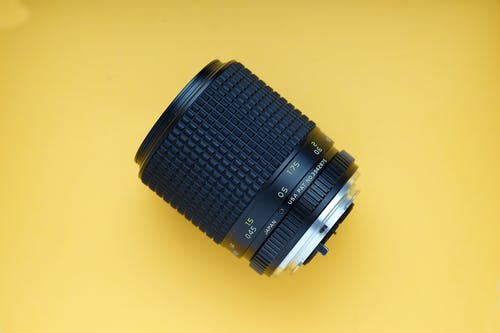Black Dslr Camera Lens On Yellow Surface