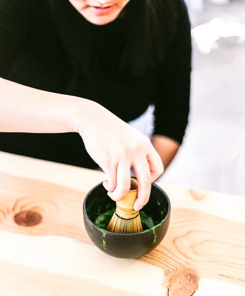 Person Holding a Bamboo Whisk in a Black Bowl Close-up Photography