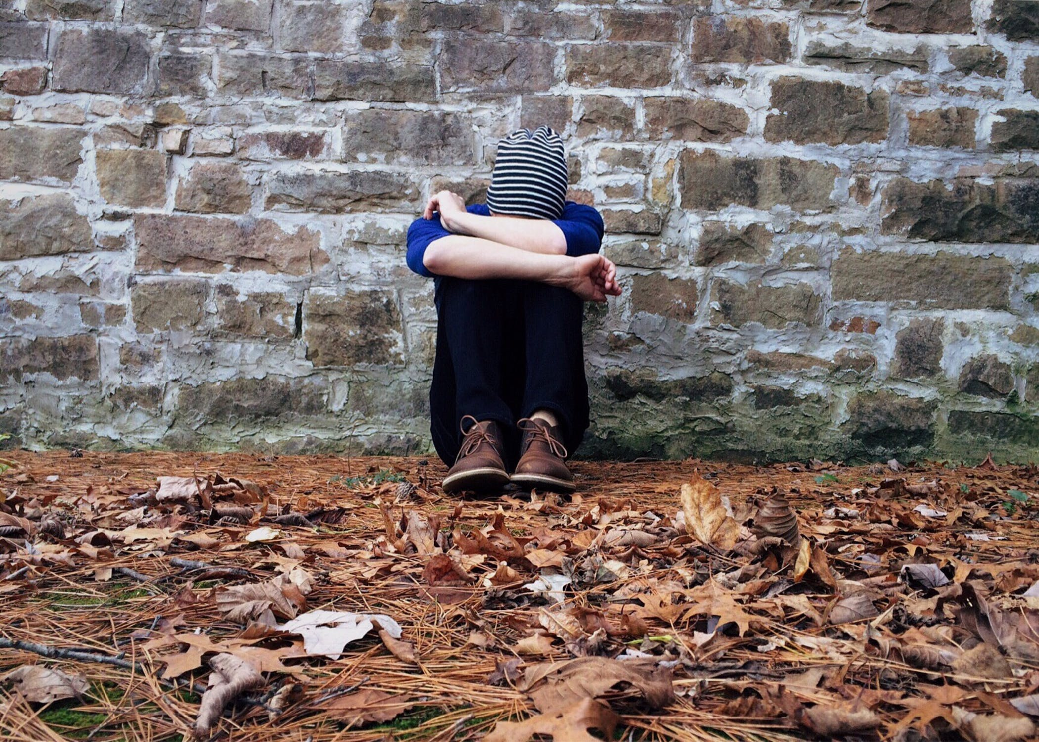 A person sitting against a wall with their head tucked between their knees