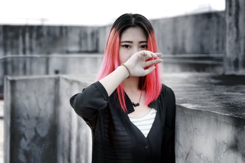 Pink Haired Woman Standind Near Concrete Wall
