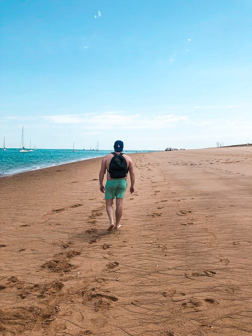 Photo of Man Walking on Beach