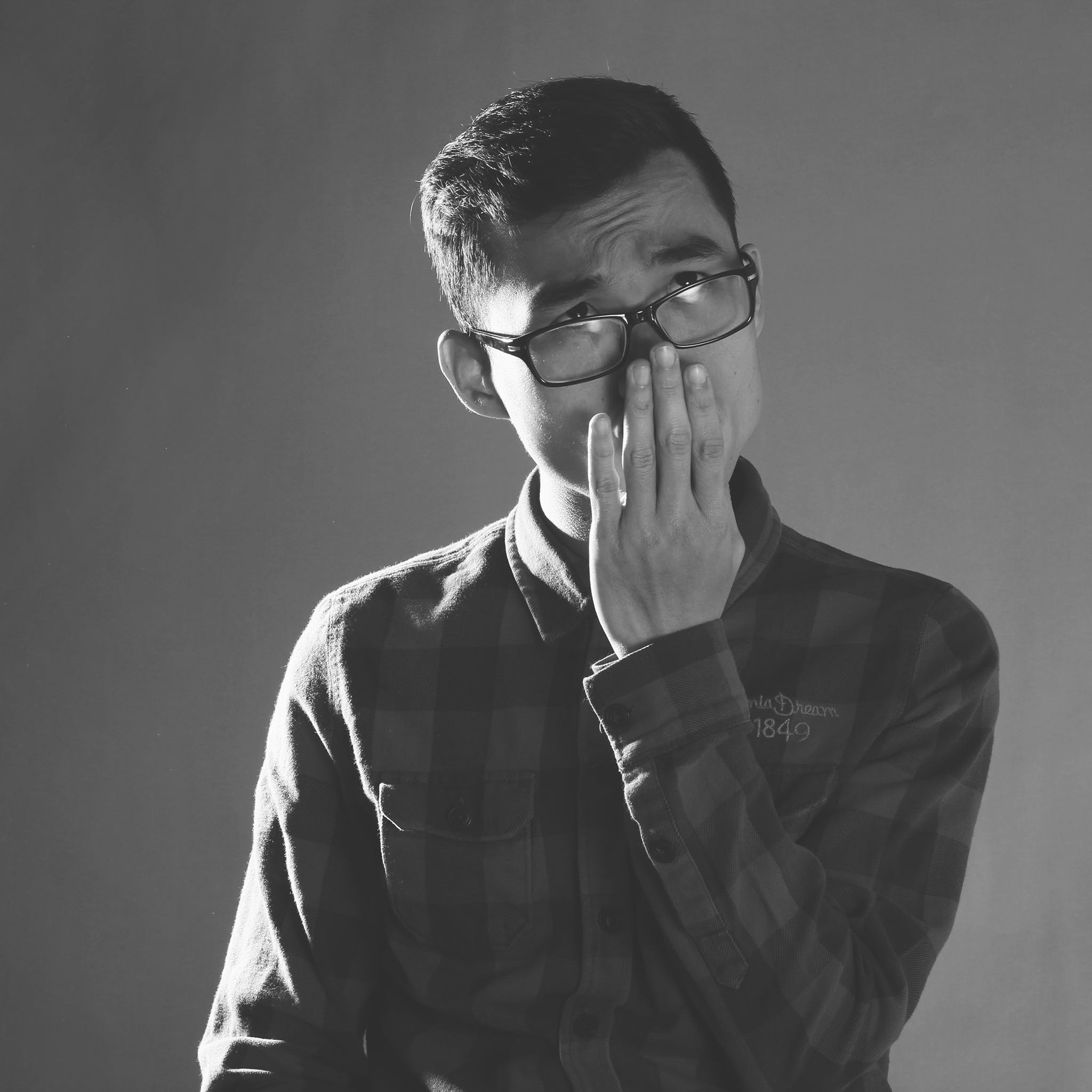 Grayscale Photography of Man Wearing Eyeglasses