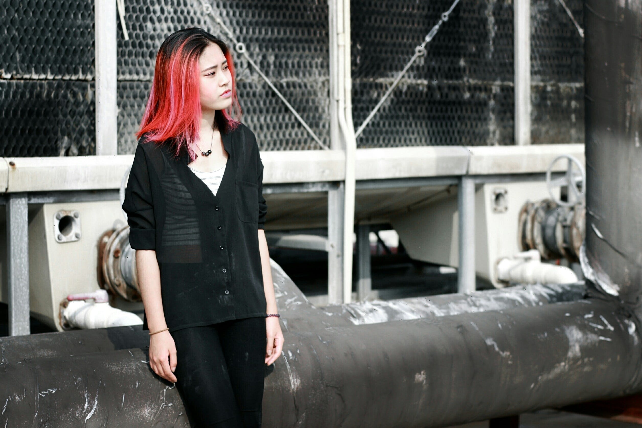 Red-haired Woman Wearing Black Top Standing in Front of White Building