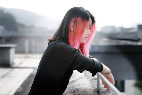 Selective Focus Photography Pink and Black Haired Woman on Bridge