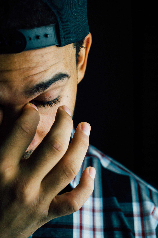 Man Pinching Nose Close-up Photo