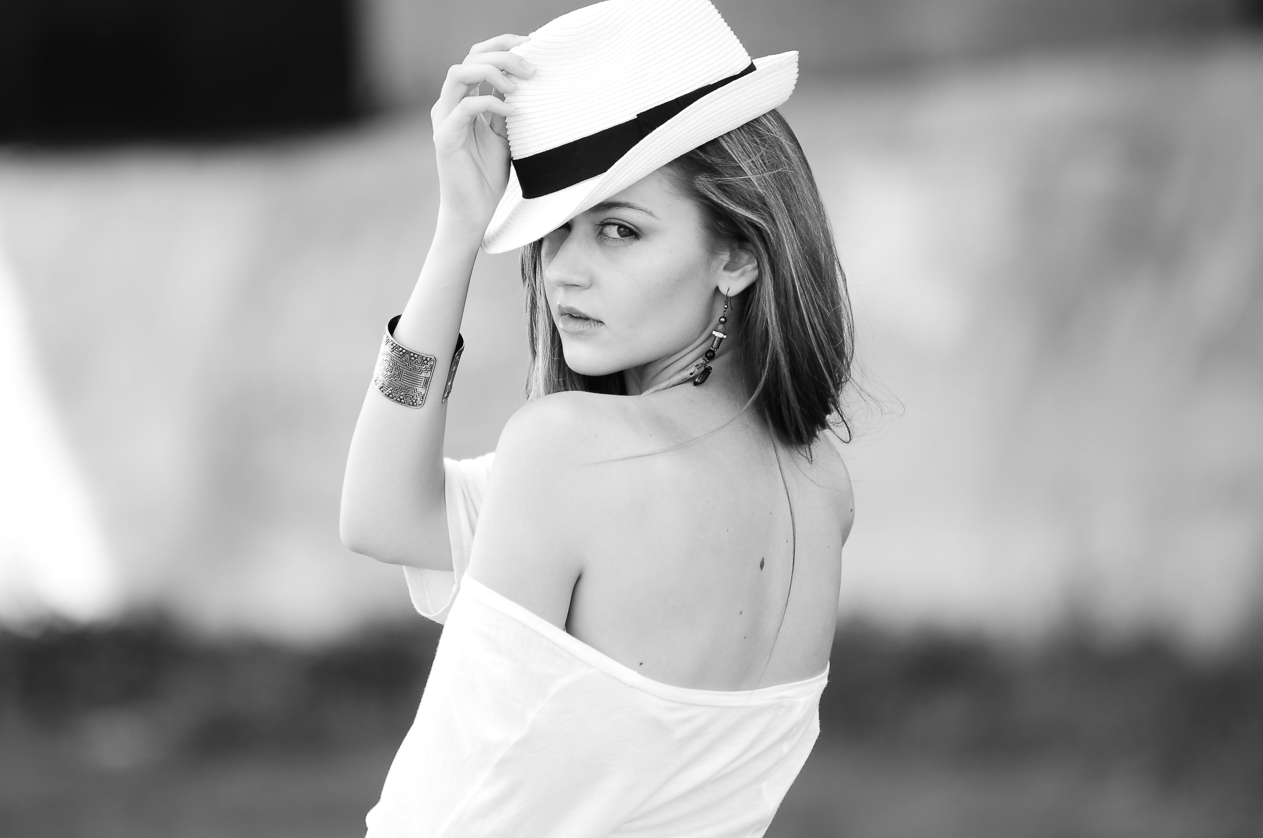 Grayscale Photography of Woman Holding Fedora Hat