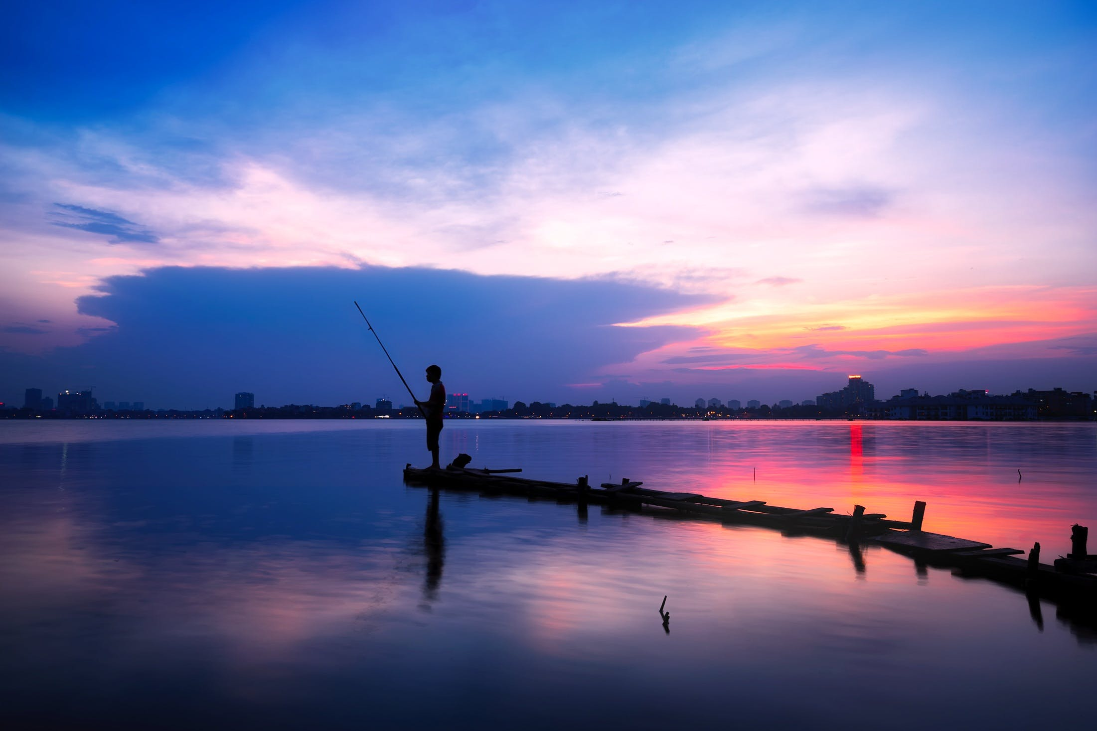 Silhouette of Man Holding Fishing Rod on Body of Water