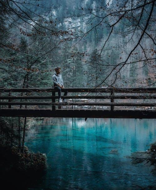 Man in Black Jacket and Blue Denim Jeans Standing on Wooden Bridge over River