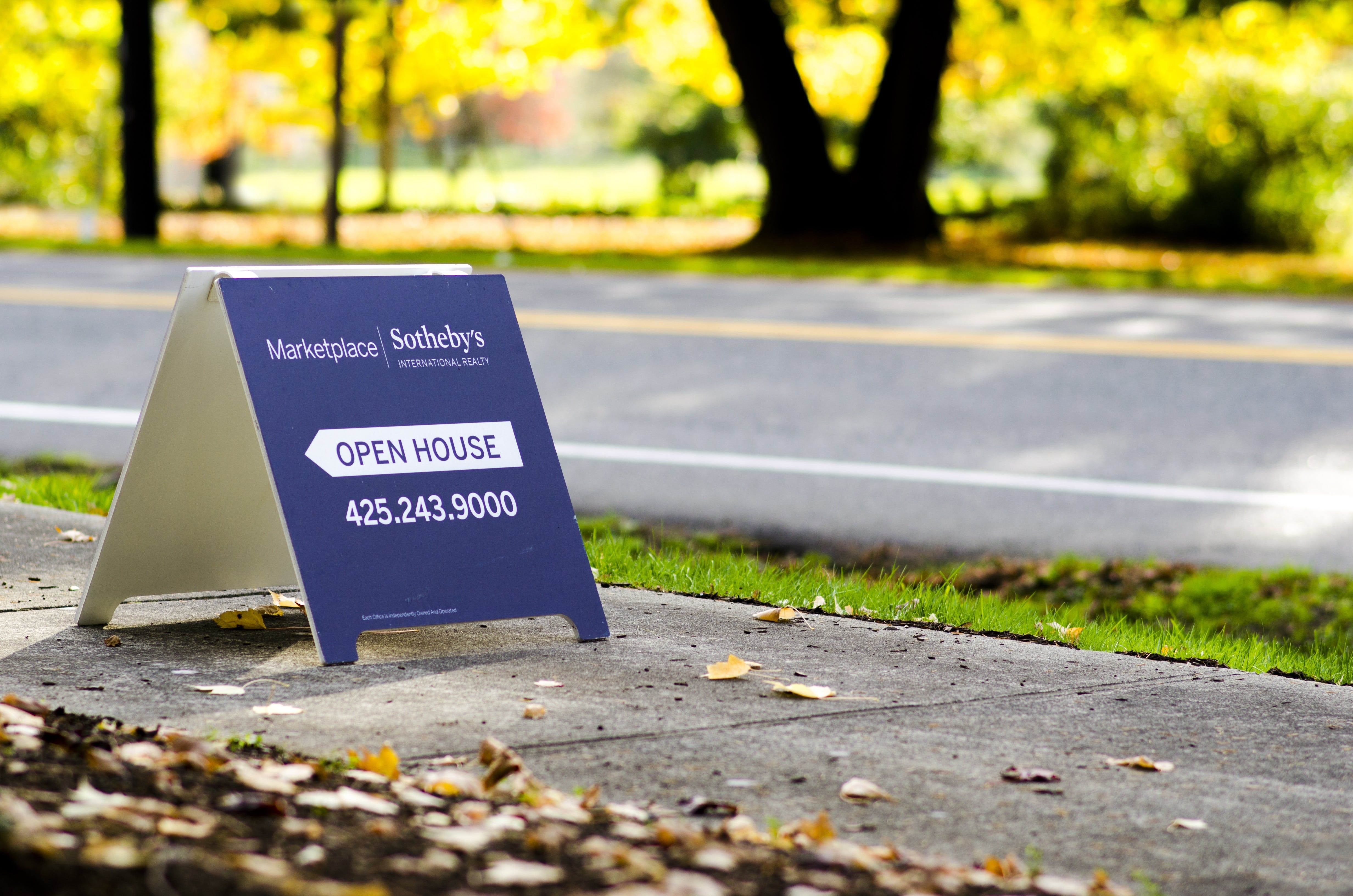 Blue Open House Stand Board on Concreted Road