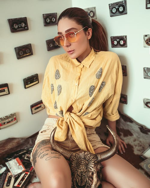 Woman Sitting down  wearing  Sunglasses and Yellow Front-tie Button-up Shirt