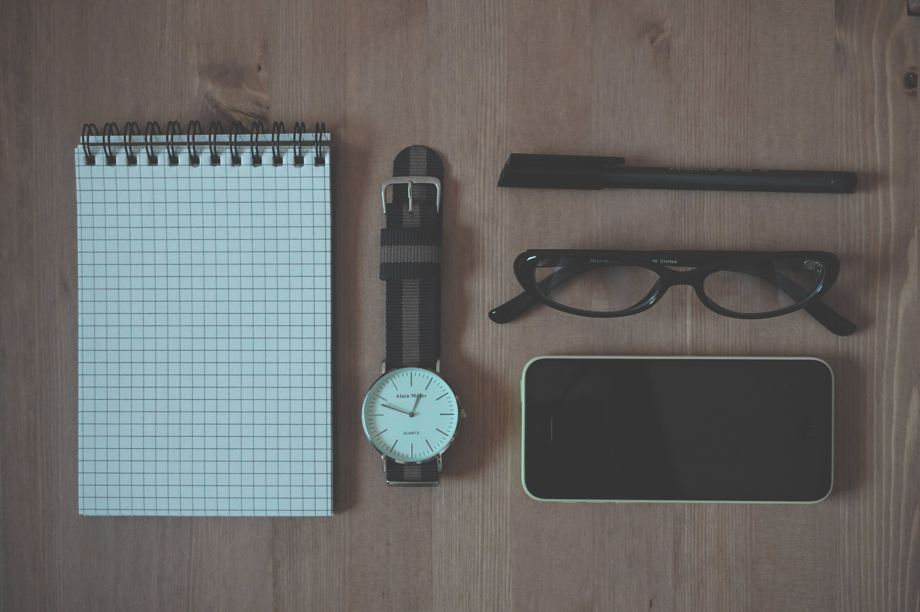 Flat Lay Photography of Graphing Notebook, Watch, Smartphone, Pen, and Eyeglasses