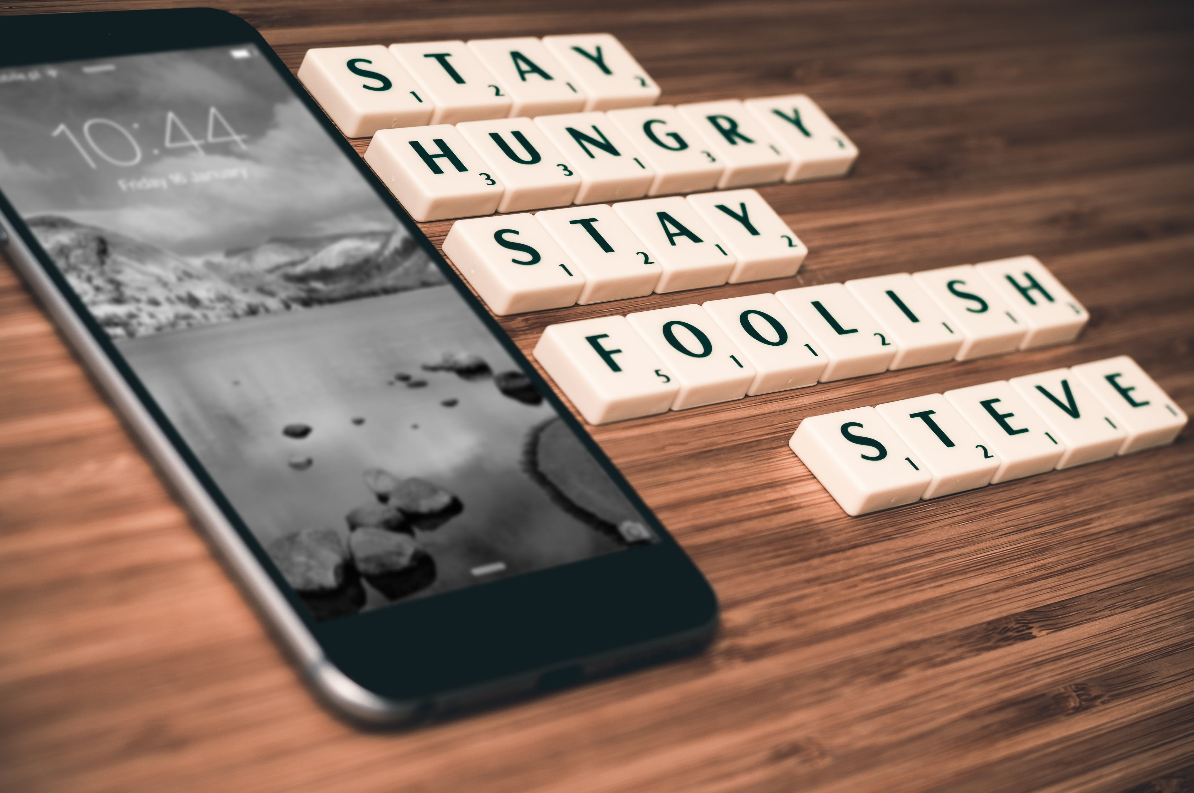 Turned-on Space Gray Iphone 6 Beside Scrabble Chip With Stay Hungry Stay Foolish Steve Text on Table