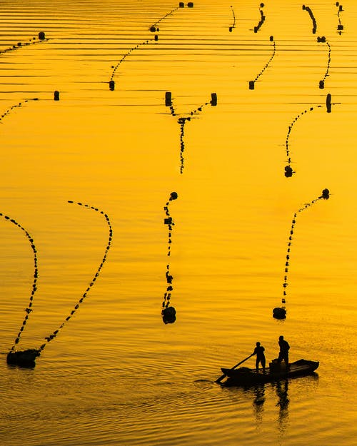 Two Men on Boat in Lake With Fish Pens at Sunset
