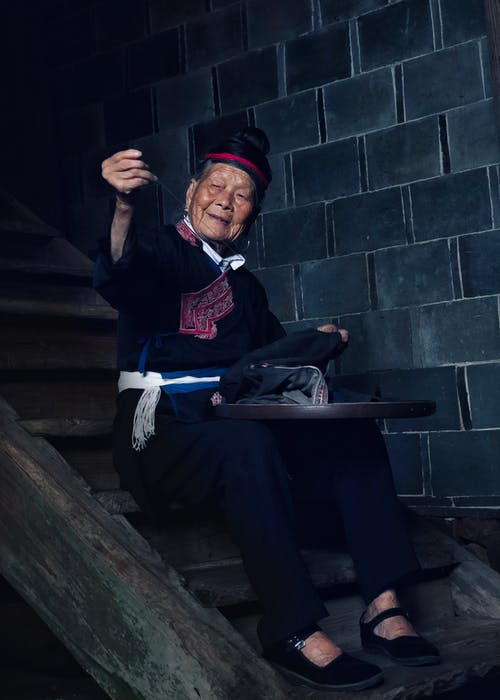 Photo of an elderly woman sitting on wooden stairs  sewing a cloth