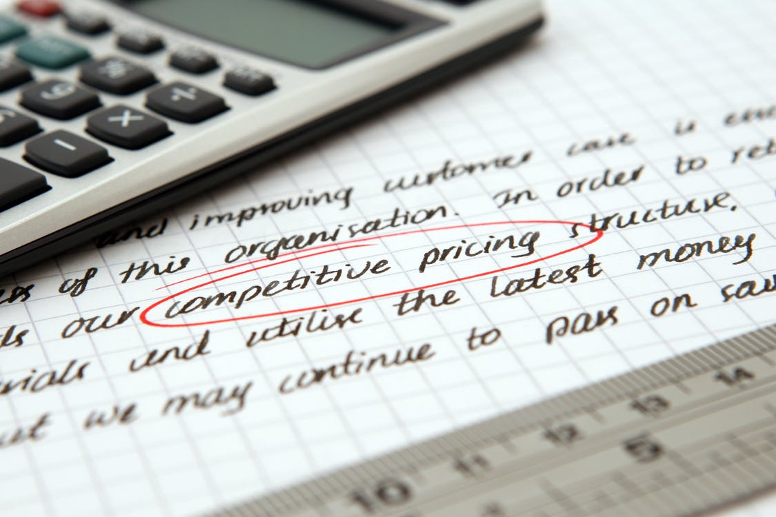 Competitive Pricing Handwritten Text Encircled on Paper