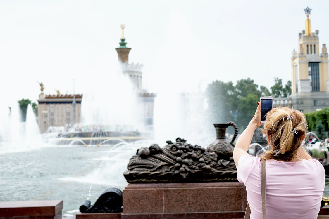 Woman Taking A Picture Of Fountain