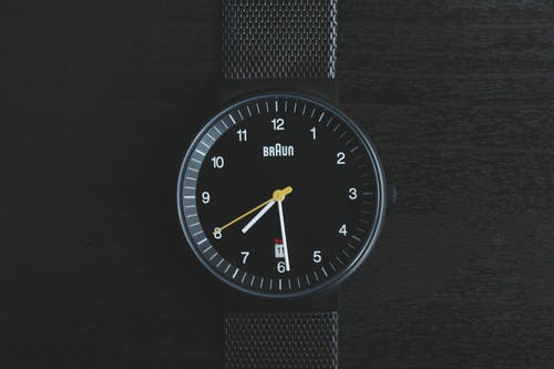 Round Black Braun Analog Watch Displaying 7:29 Time