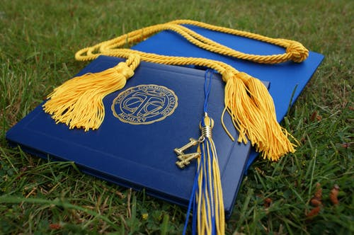 Diploma and Square Academic Hat on Grass Field