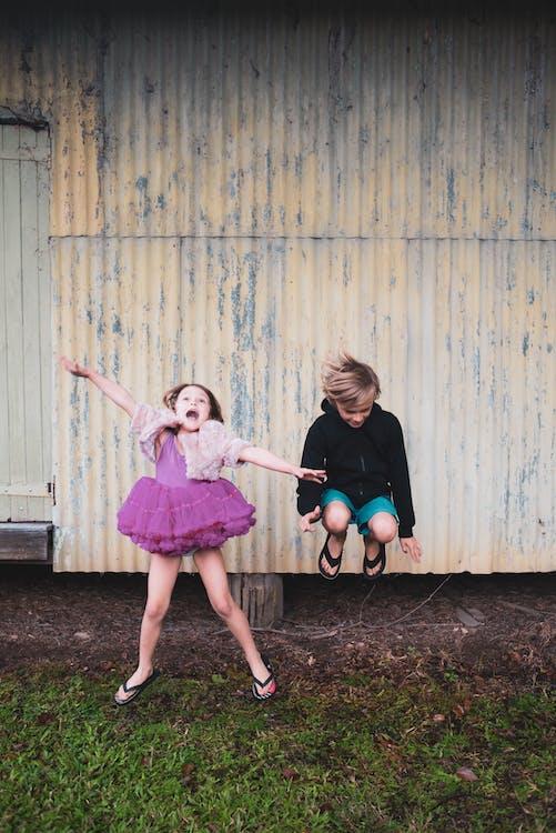 Photo Of Boy Jumping Beside Girl