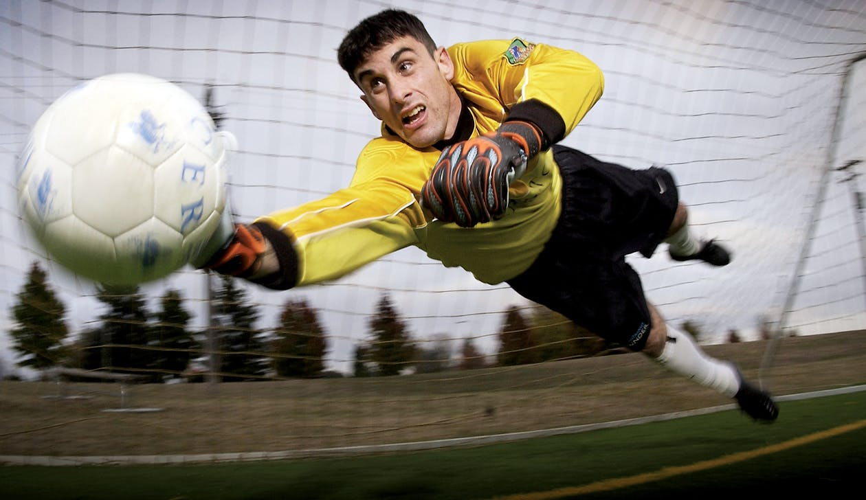 Man Catching Soccer Ball on Field