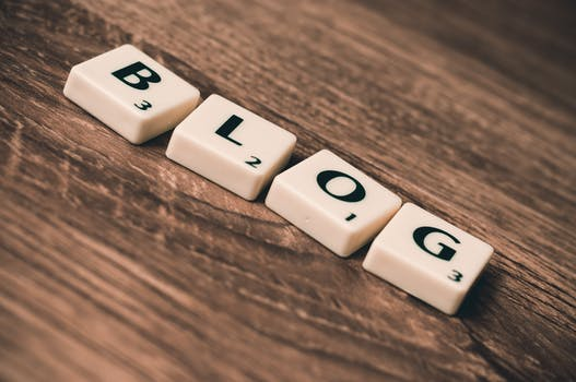 A veneered table top with 4 ivory casts on which are written BLOG to signify List of 49 benefits of blogging for the blogger and the host blog