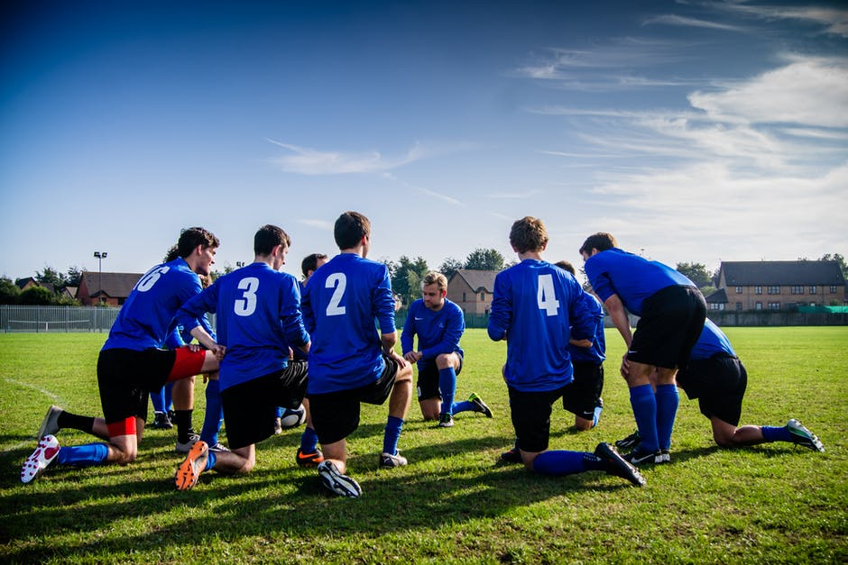 Group of Sports Player Kneeling on Field