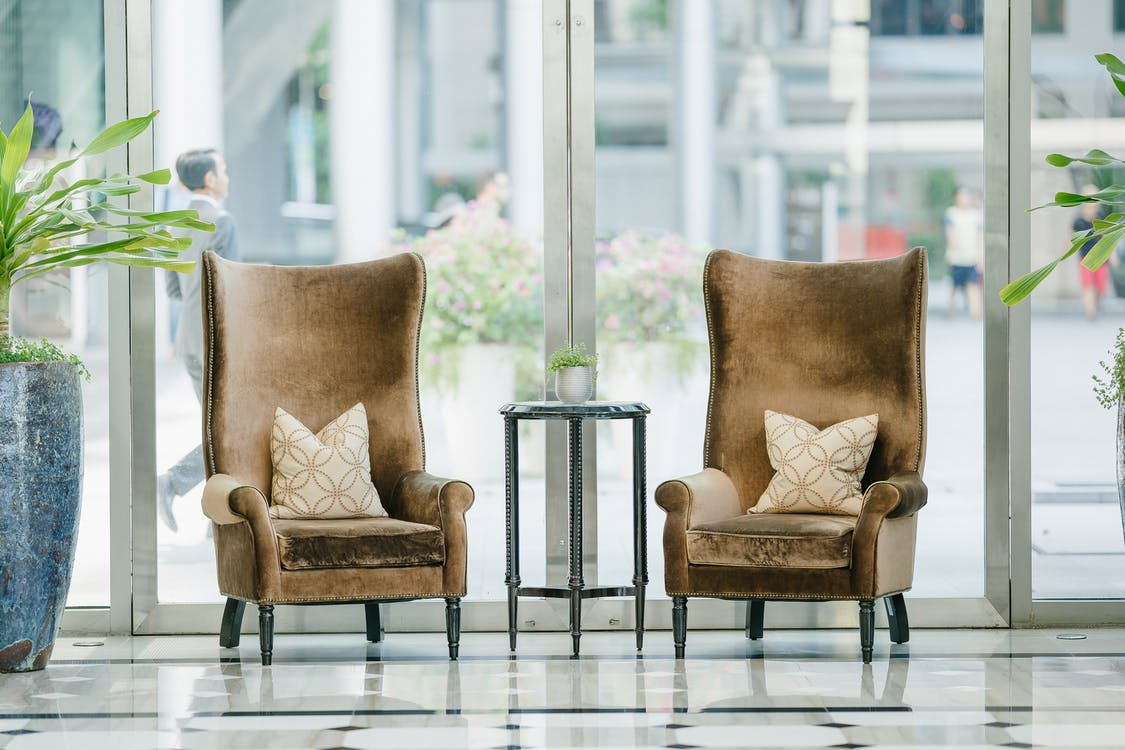 Photo of two brown sofa chairs near glass window