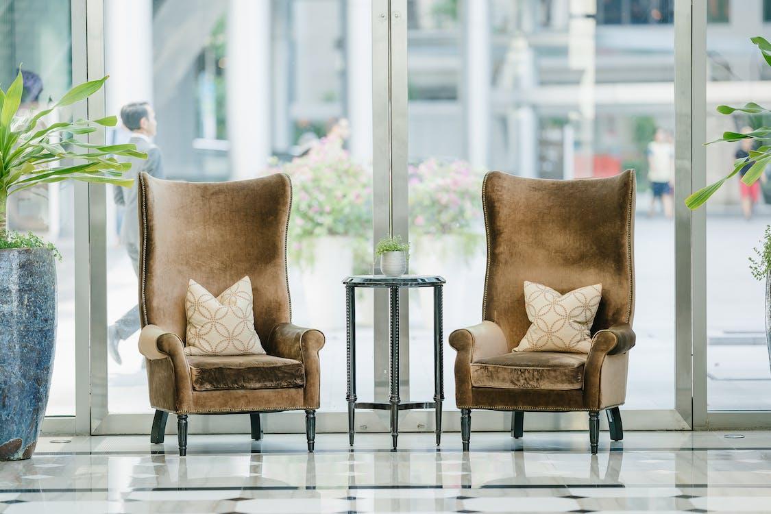 Photo of two brown sofa chairs near glass window
