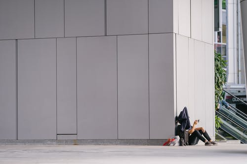 Person Sitting down beside White Concrete Wall