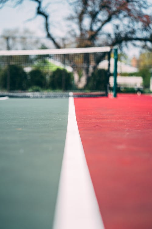 Selective Focus Close-up Photo of Empty Red and Green Tennis Court With View of Tennis Net