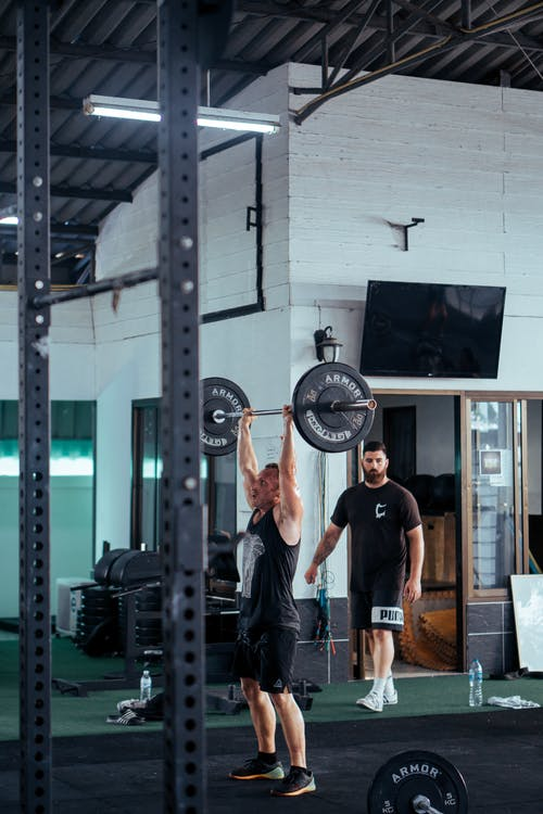 Man In Black Tank Top Lifting Barbell At The Gym