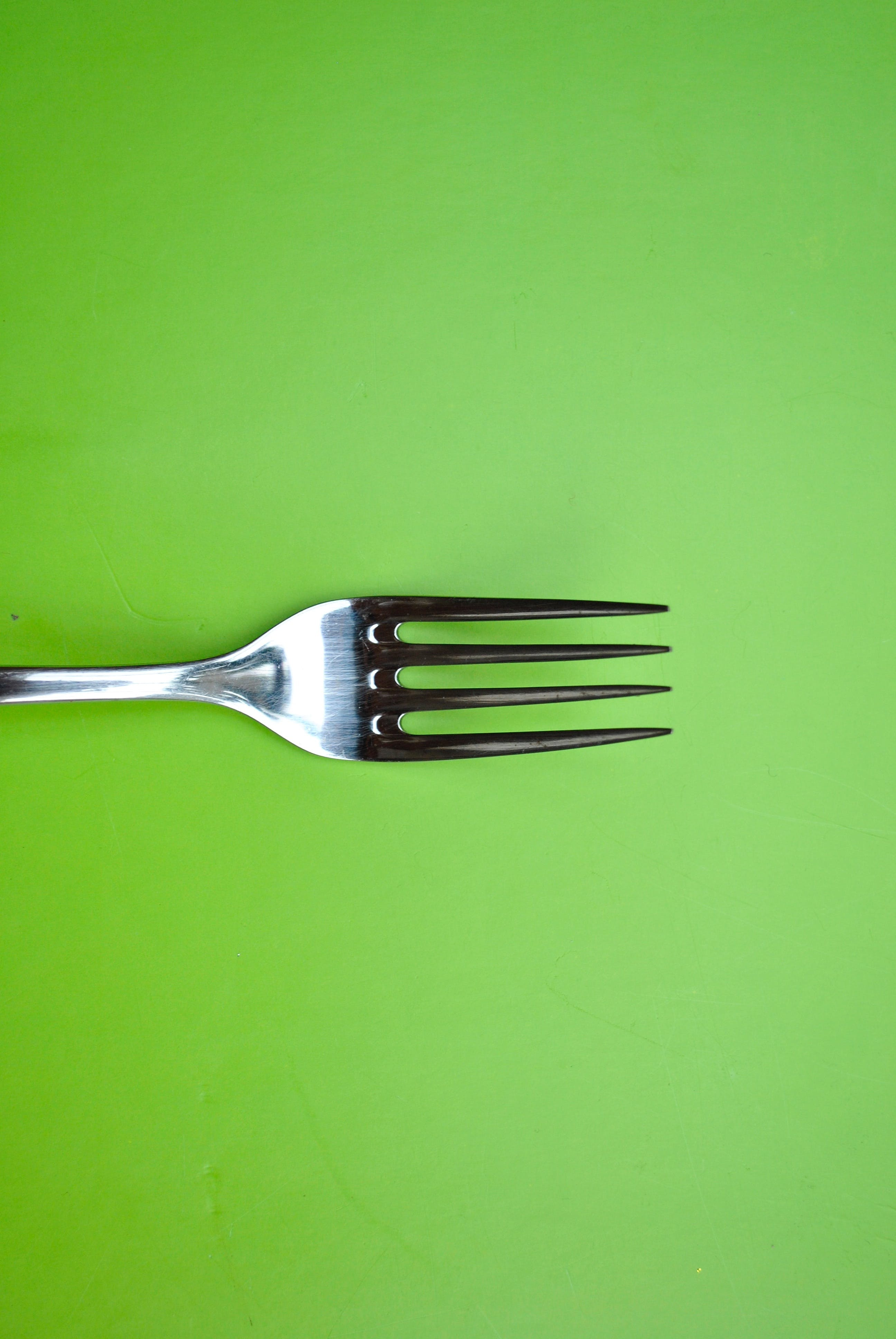 Stainless Steel Fork on Green Paper