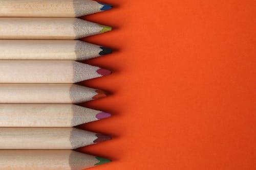 Бесплатное стоковое фото с оранжевый фон, цветные карандаши