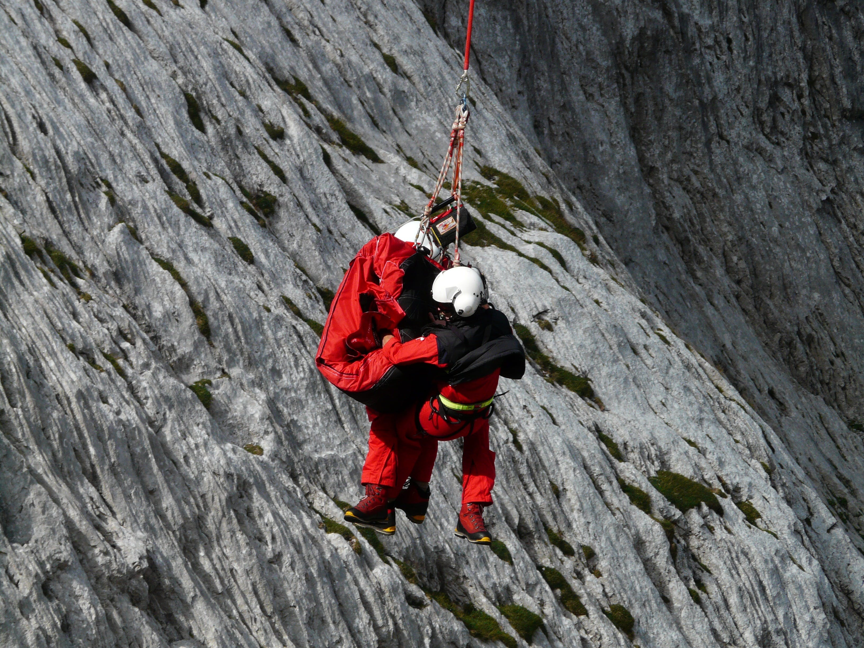 Two People Rappelling Near Grey Rocks