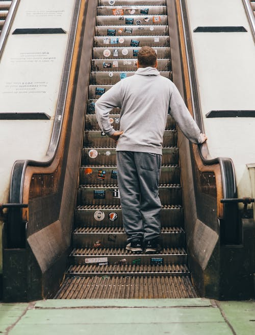 Back View Photo of Man Standing on Escalator