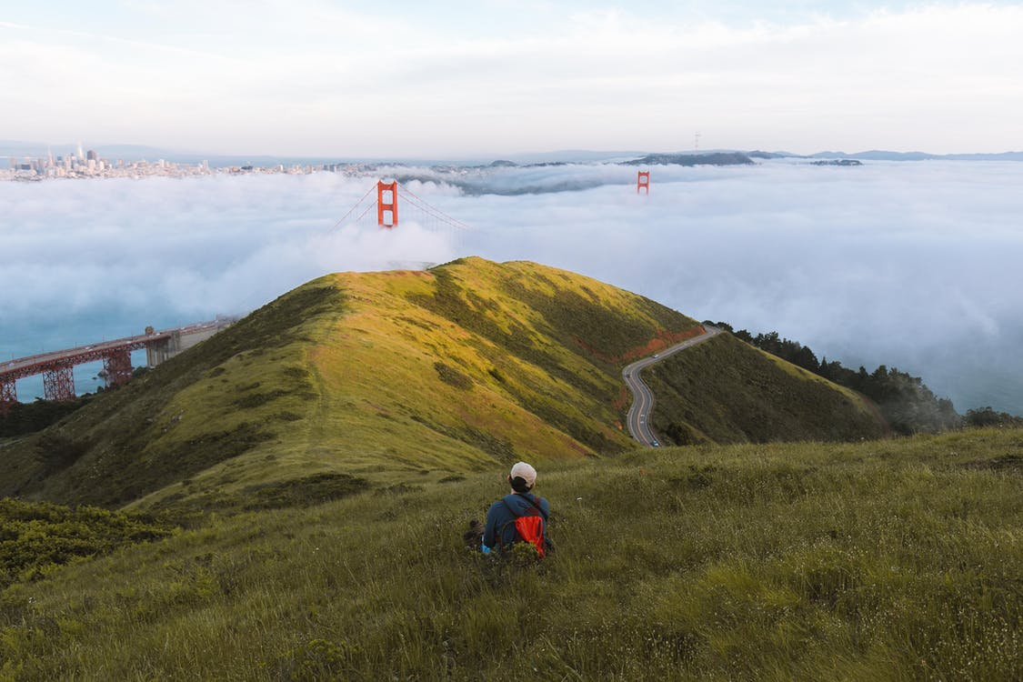 Person Sitting On Grass Hill Near The Golden Gate Bridge In San Francisco d