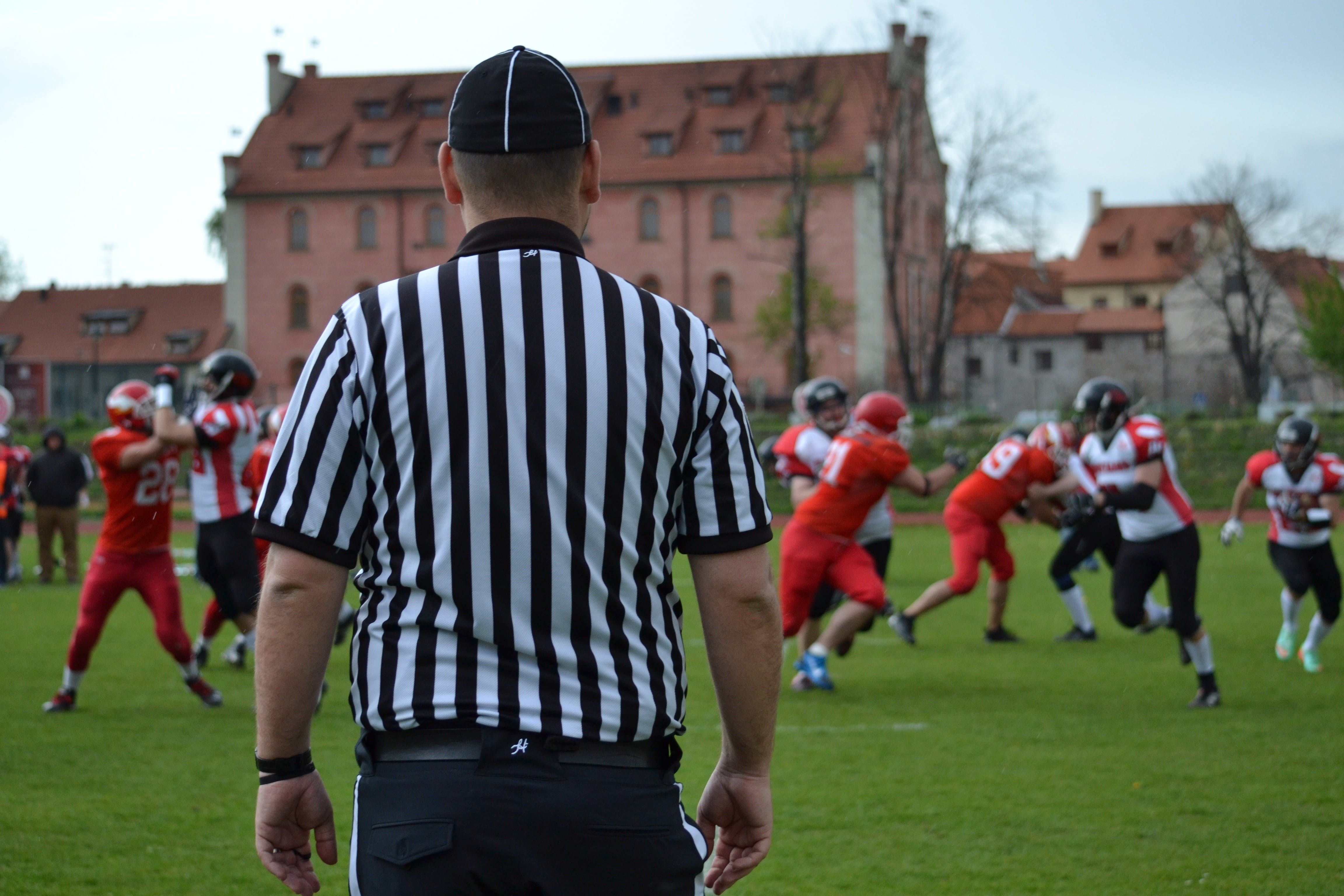 Free stock photo of American football, black and white clothing, contact game, referee