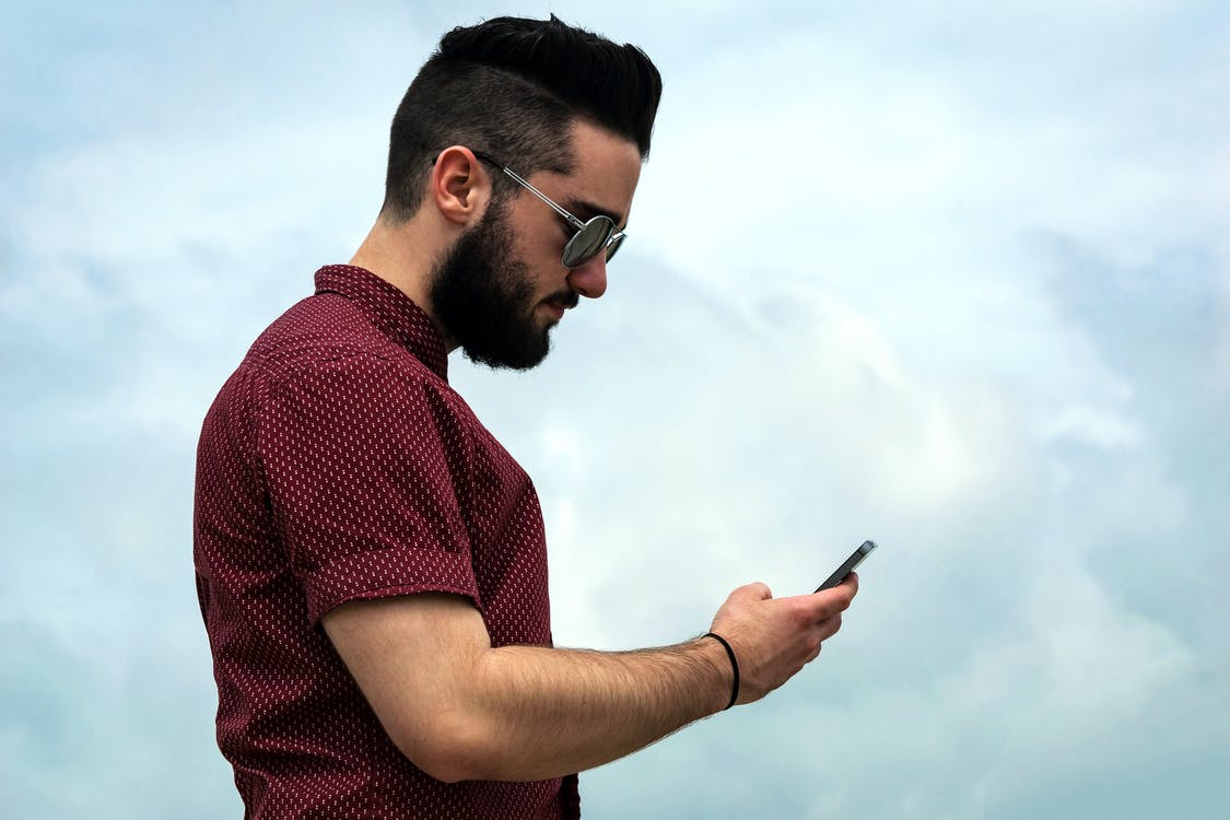 Selective Focus Photography of Man Holding Smartphone