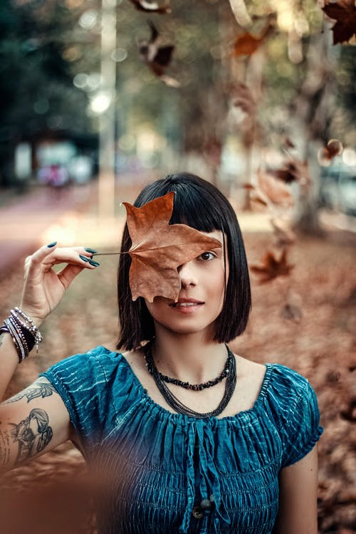 Photo Of Woman Holding Dry Maple Leaf