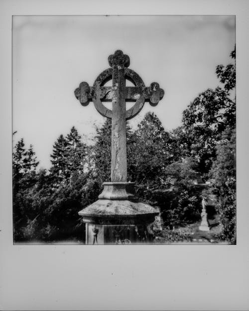 Grayscale Photo of Concrete Cross Near Trees