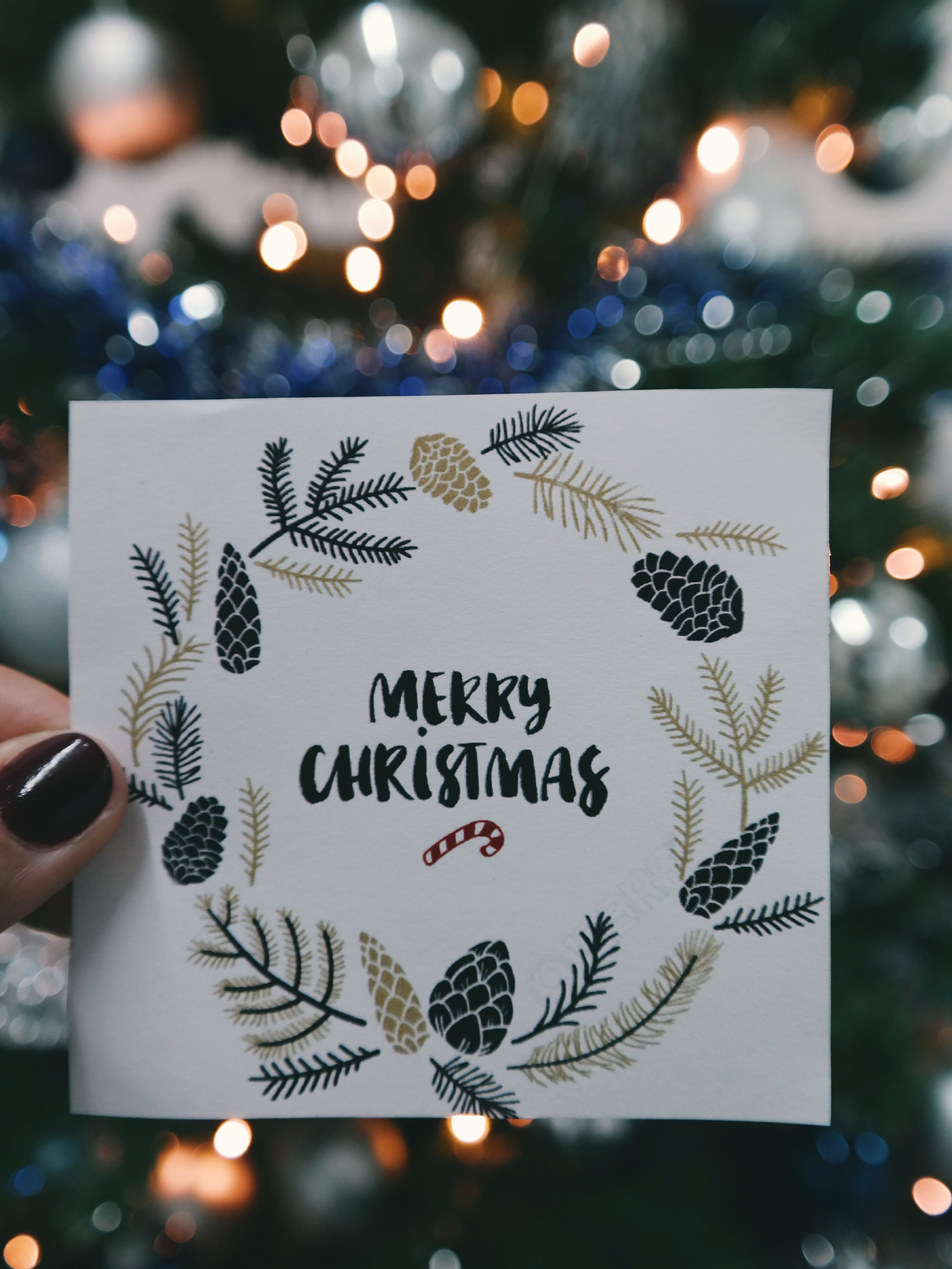 Person Holding Beige and Black Floral Merry Christmas Card