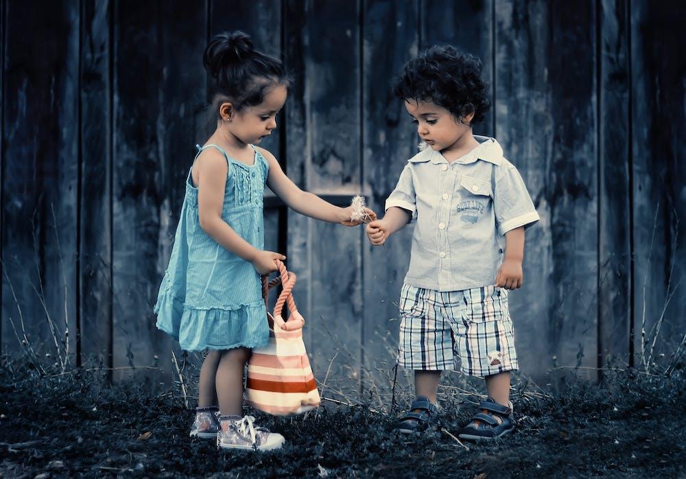 Garçon et fille debout près du mur | Photo : Pexels