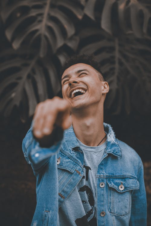 Selective Focus Photo of Man in Blue Denim Jacket Posing With His Head Back Laughing While Pointing Finger