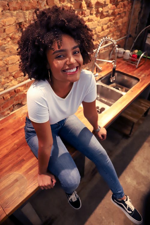 Cheerful young lady sitting on kitchen countertop