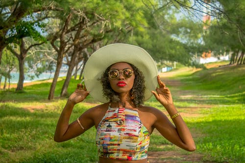 Portrait Photo of Woman in Sun Hat, Crop Top, and Sunglasses Posing