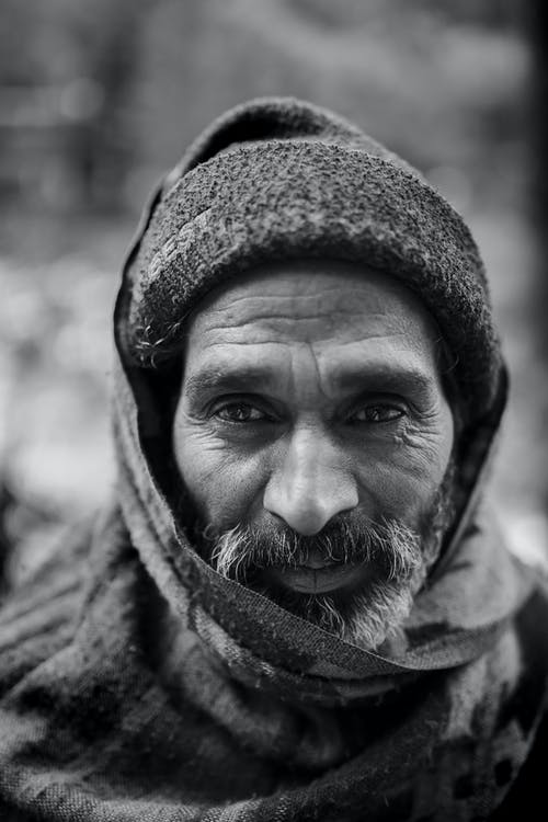 Selective Focus Grayscale Portrait Photo of Elderly Man in Beanie and Scarf Over His Head