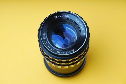 Black camera lens against a yellow background