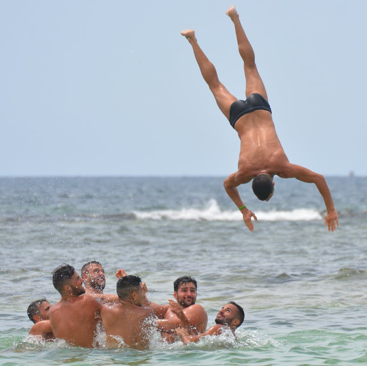 Man Diving on Body of Water Near of Group of Men