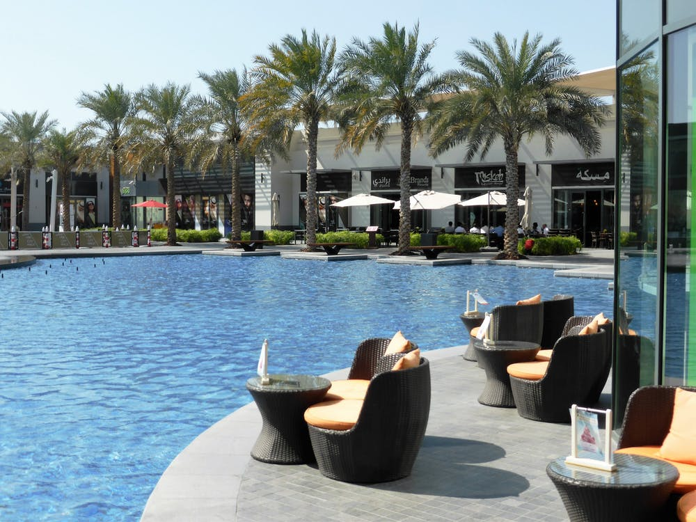 Round Black Wicker Table With Two Chairs on Poolside